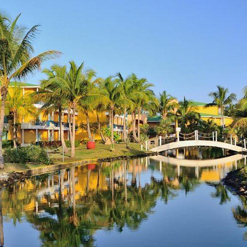 Hotel con palme, fiume e ponte